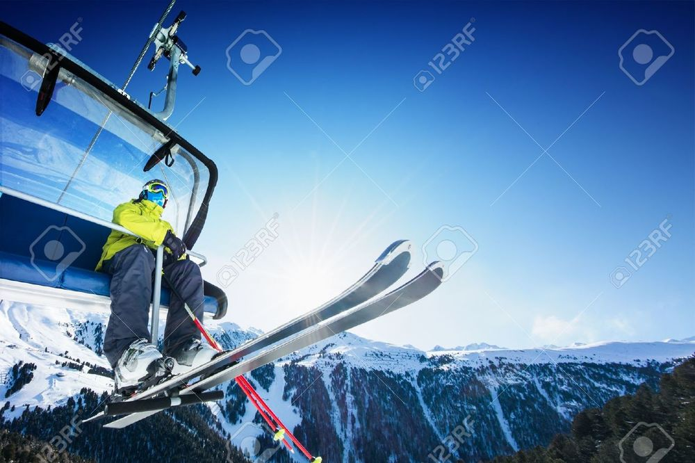 17753055-Skier-siting-on-ski-lift-lift-at-sunny-day-and-mountain-Stock-Photo.jpg