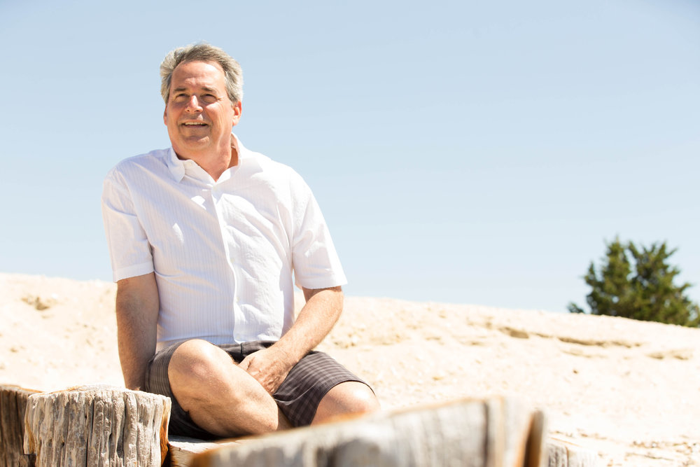 Portrait of Kevin sitting on the beach with weathered wood in the foreground.
