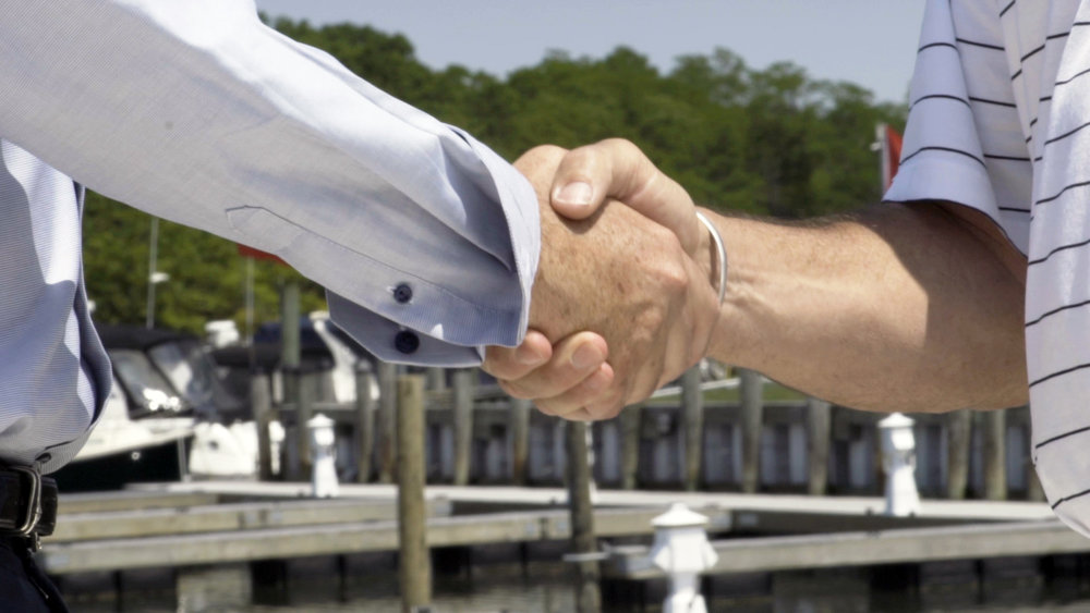 Handshake over a maritime background.