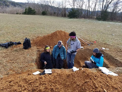 Sam, a grad student from Auburn University, explaining soil horozons to Hannah, Kathleen, and Me.