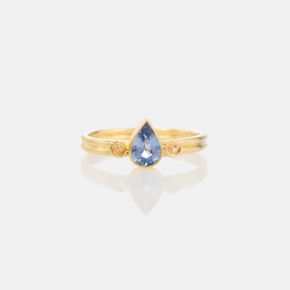 An all natural blue sapphire with two yellow sapphires handcrafted in 18 karat yellow gold.