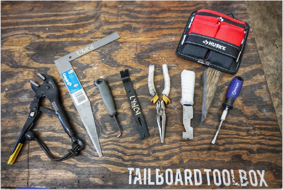 Tools pictured from left to right: Vice grips, Modified framing square, DIY Key tool, Flat pry bar, needle nose pliers, DIY shove knife, wooden chock, flat head screwdriver.