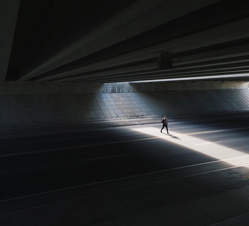 Walking across street under a bridge by a social media photographer