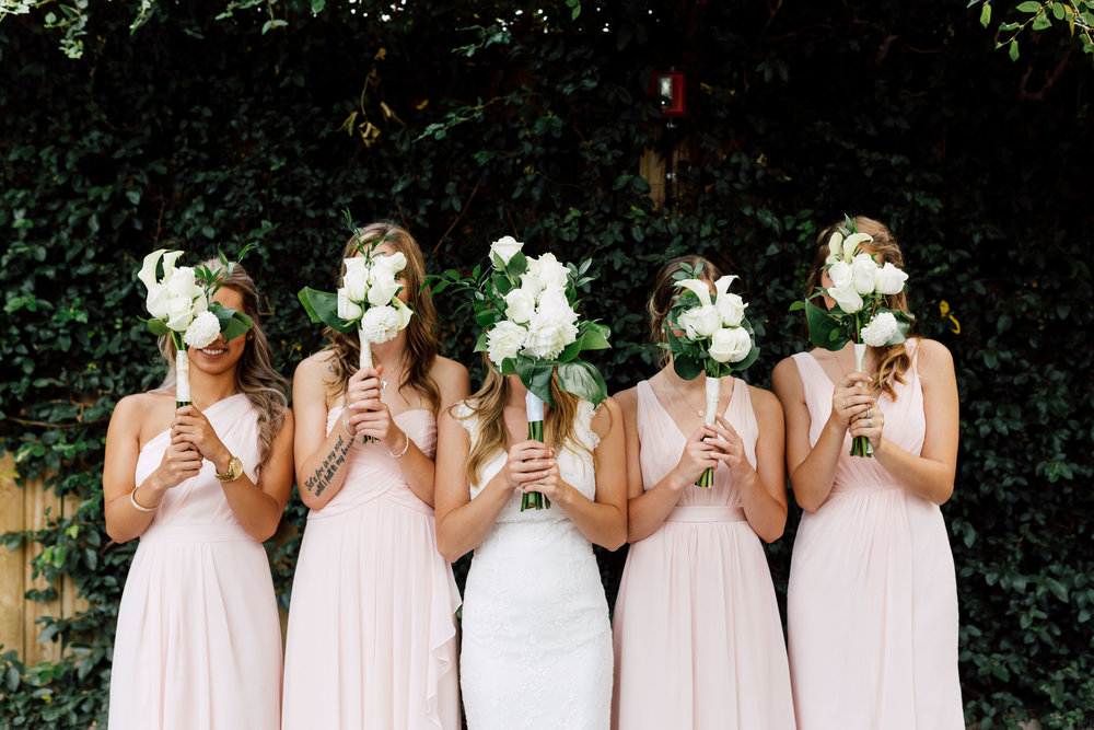 Bride and bridesmaids hiding faces behind their bouquets