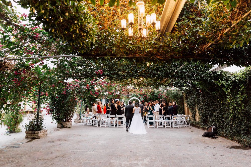 Couple walking down aisle from behind at a wedding at madsens greenhouse in toronto