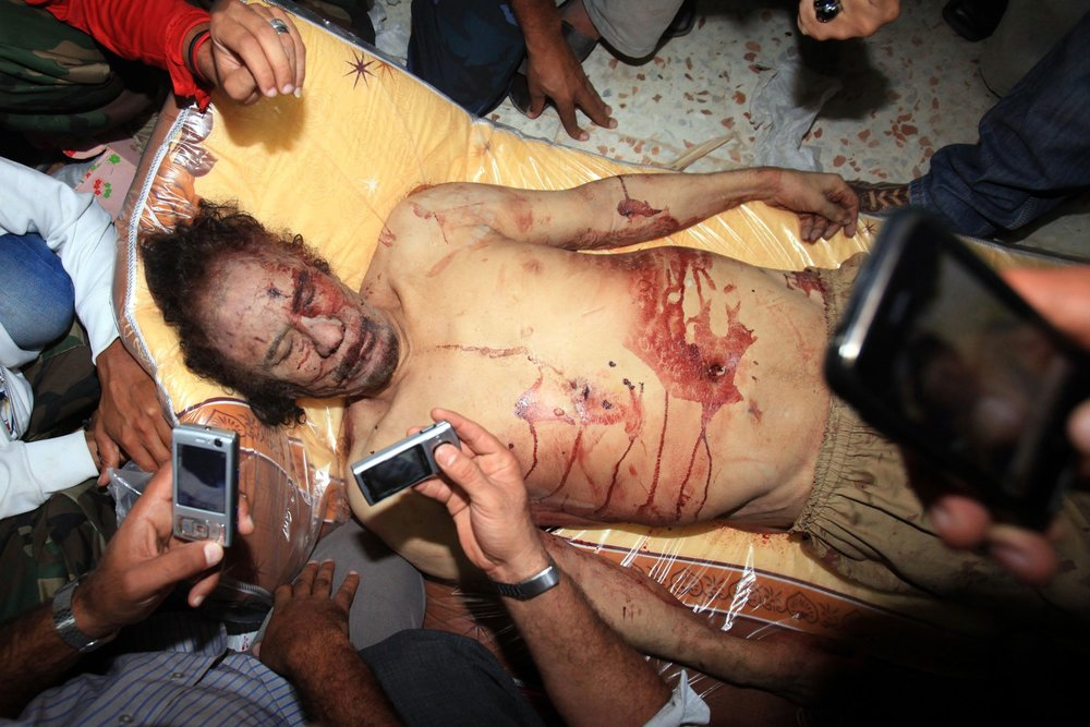 Libyans take pictures with their mobile phones of the body of Moamer Kadhafi in Misrata on Oct. 20, 2011. (credit: Mahmud Turkia)