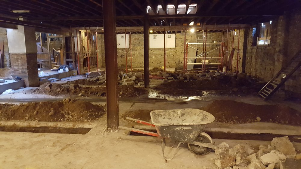 New concrete walls divide the basements of the five houses. Here, you can see the trenches for the new footings, as well as the existing steel columns and beams.
