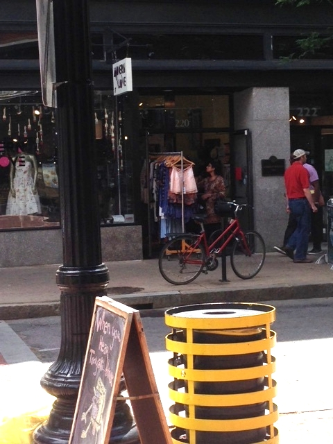 See the bike parked outside of this clothing store.  Walkers and bikers were everywhere on the streets.  Cars did not speed past, drivers watching out for pedestrians and scanning what was happening outside on the streets.