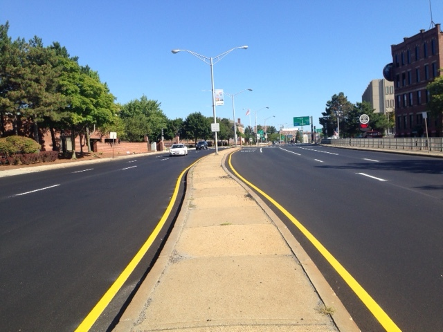 "I waited to see where the painted lane lines would go.  Guess what?  The lines were still in the very same place they were before the road was re-done!  It still remains a six lane ""freeway"" right in the downtown -- so wide that it remains difficult to cross on foot and unsafe to traverse on a bicycle.   Some questions:  DPW, where is the community input on how the road was re-designed?  Where is the imagination of what this road could have become and how it could have been re-designed to work for everyone - car drivers, walkers, bus riders, bicyclists?  Also, check out the median strip made completely of desolate-looking concrete.  Wouldn't walkers be more enticed if we added grass or plantings here?  If we want to have more pedestrian activity, we need to create a more aesthetically appealing experience for people who prefer to walk."