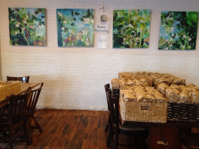 Gallery space for displaying the artwork of local artists.  The bags of fresh bread that have just been baked will soon be sent to restaurants throughout the city.