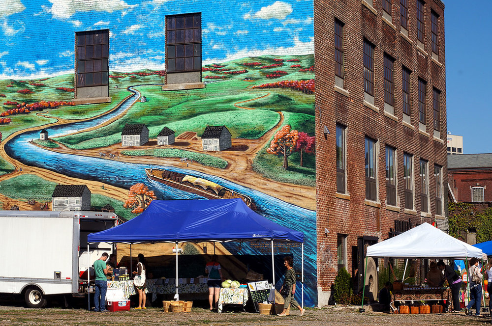 A bit of creative placemaking... This mural painted on the exterior back wall of Crompton Place depicts this neighborhood's connection to the waters of the Blackstone canal and river.