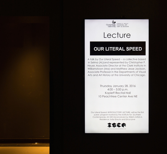 "Our Literal Speed presents ""Our Literal Speed,"" dimensions variable, materials: two-person lecture,publicity displayed continuously on video monitor installed in wall, Institute for Southern Contemporary Art, Georgia State University, Atlanta, 28 January 2016 (detail)"