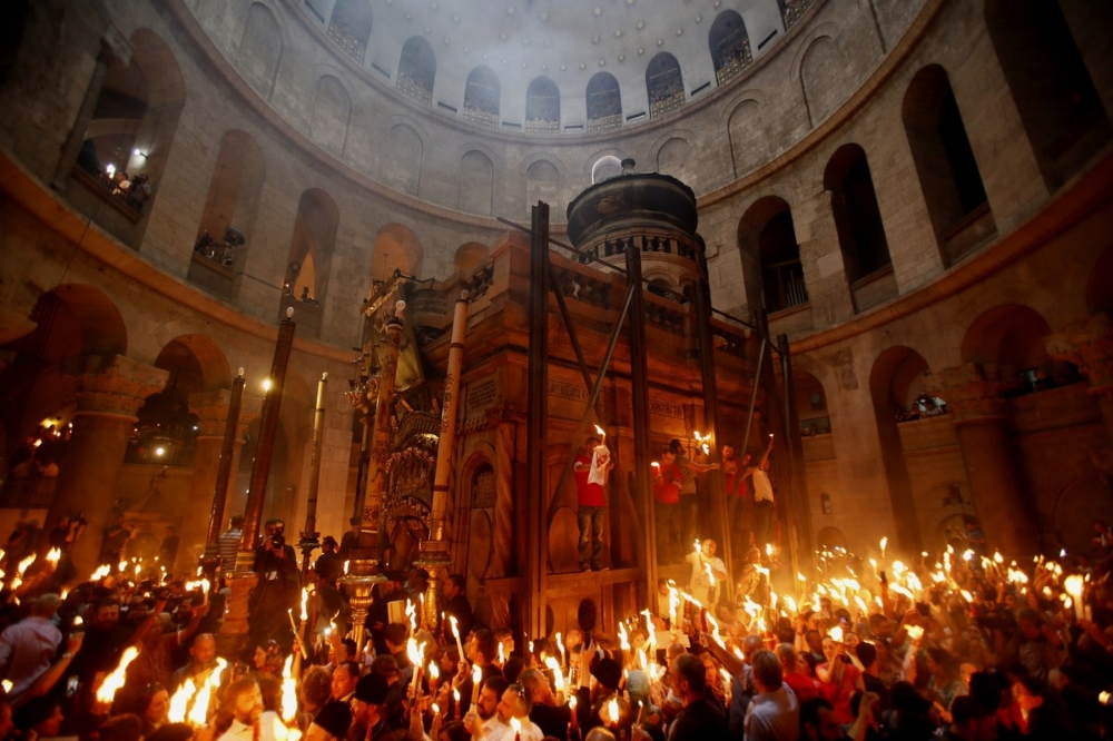Christian Orthodox worshipers hold up candles during 'Holy Fire' ceremony on the eve of Orthodox Easter, Jerusalem, by Gail Gibbon - source