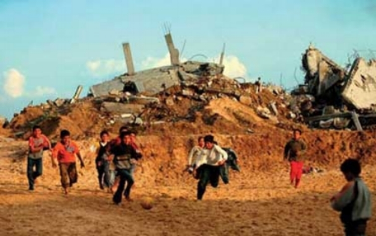 palestinian children play football beside destroyed homes in gaza strip    ( source )