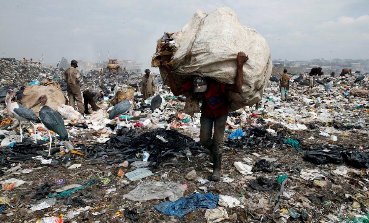 In Kenya, a man carries a big sack at the country's biggest dumpsite in the capital, Nairobi, ahead of a ban on the use of plastic bags. August 2017, Reuters ( source )