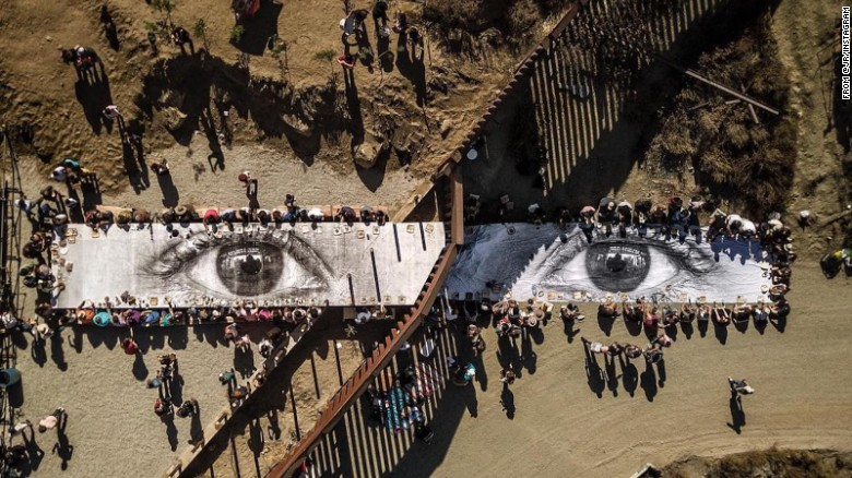 """On October 8th, for the last day of his huge scaffolding installation on the Mexican side of the border between the United States and Mexico, [anonymous French artist] JR organized a gigantic picnic on both sides of the fence. … hundreds of guests came from the US and Mexico to share a meal together. People gathered around the eyes of a Dreamer, eating the same food, sharing the same water, enjoying the same music (half of the band on each side). The wall was forgotten for a few moments ... "" ( source )  [H/T:  Plough Weekly ]"