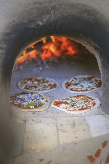 Garden pizza cooking in the cob oven.