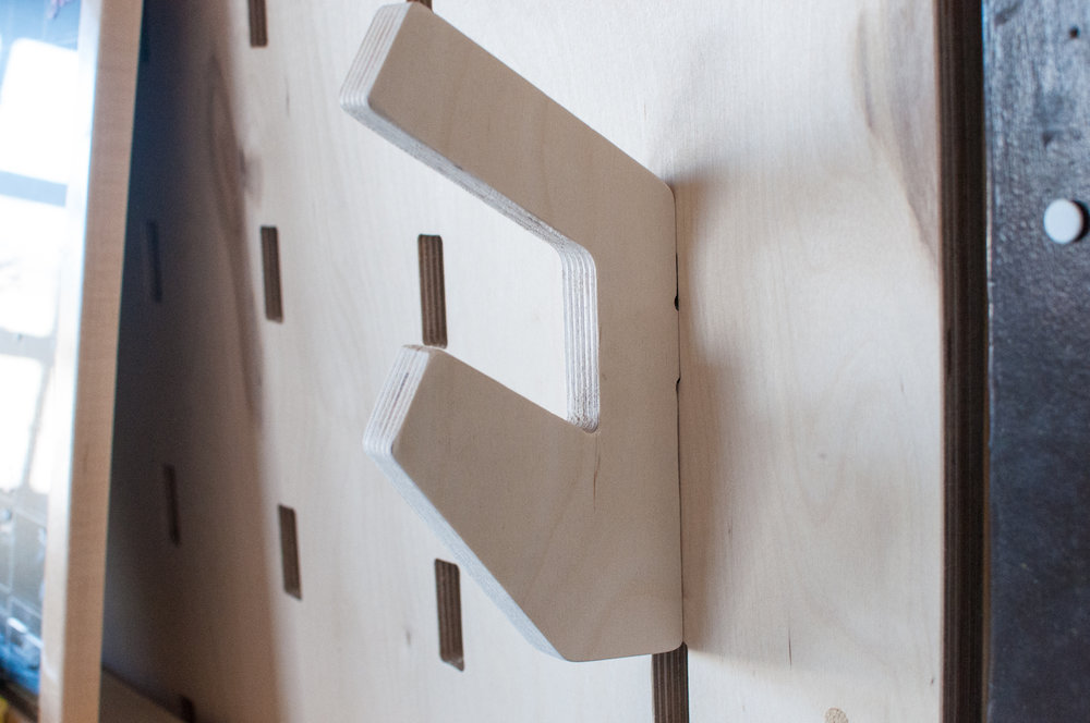 A coat hook made by Better Block slots into one of the many holes on the wall at Better Block HQ.