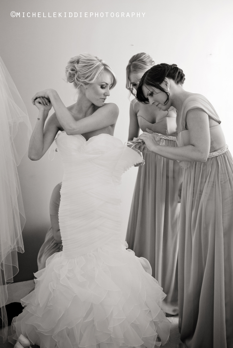 bridesmaids help bride get into wedding dress