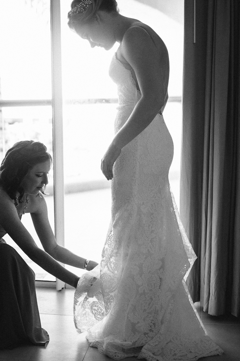 Punta Cana destination wedding, maid of honor helps bride into her wedding gown