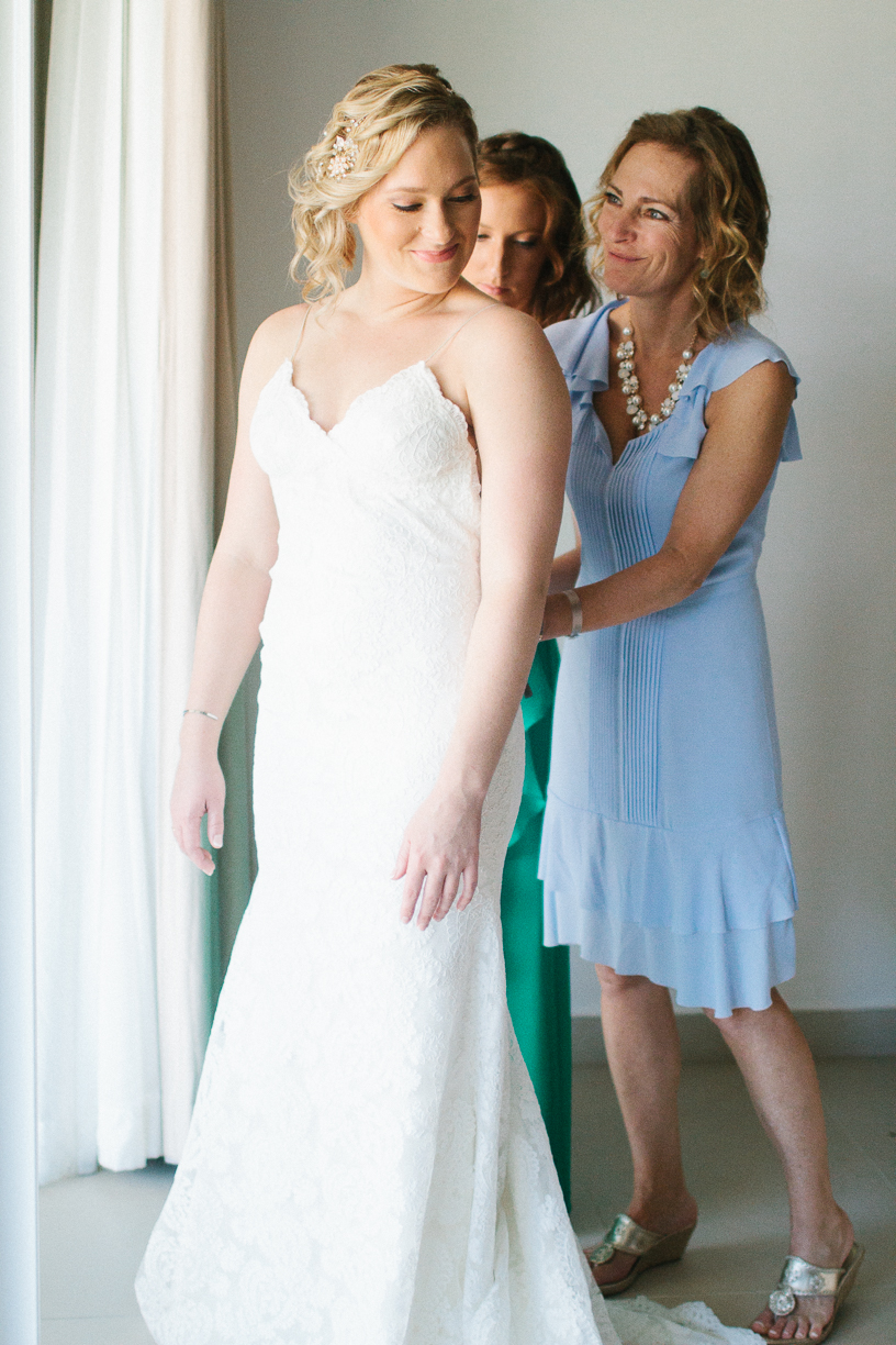 Punta Cana destination wedding, mother of the bride helps her daughter into her wedding gown