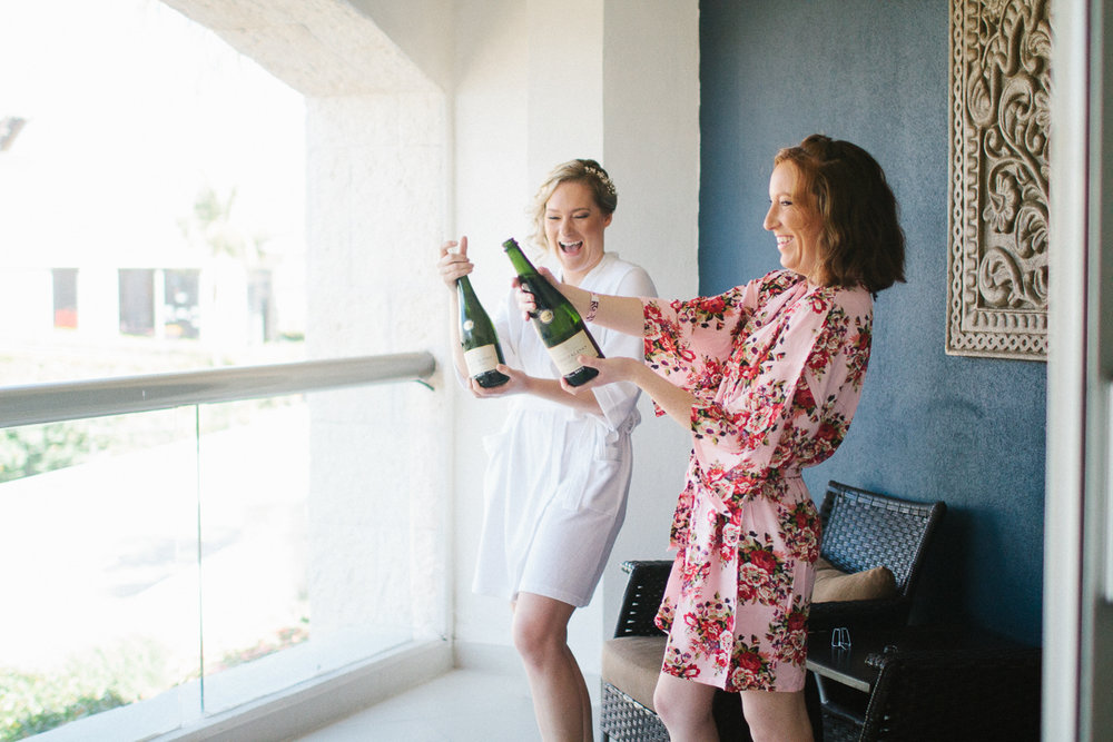 Punta Cana destination wedding, bride and her sister pop open a bottle of champagne