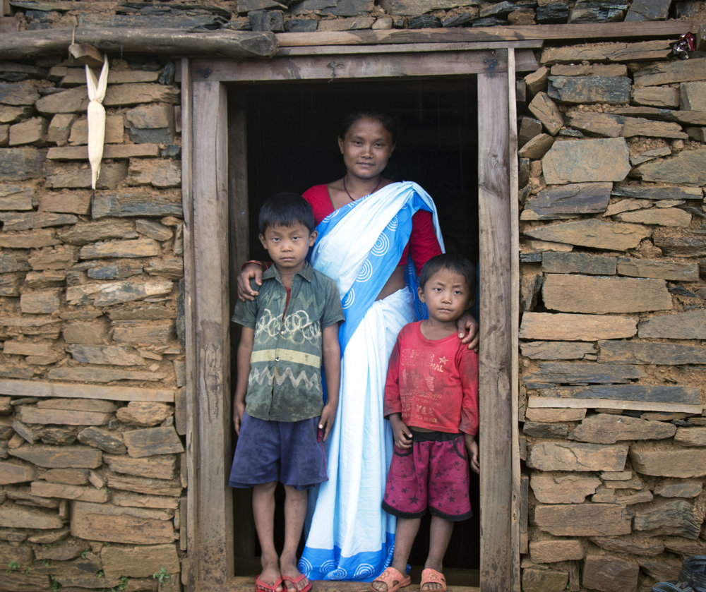 Manju poses in front of her house with her two sons