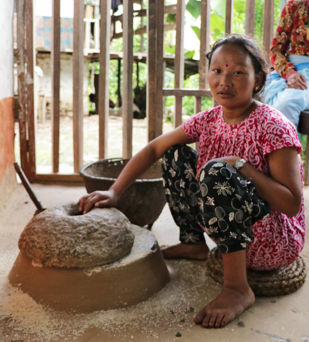 Maya grinds corn into flour by hand