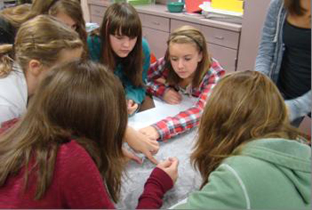 PLANNING AHEAD: This team huddled around their map and discussed the best location for their project.   Photo by Paula Farley.