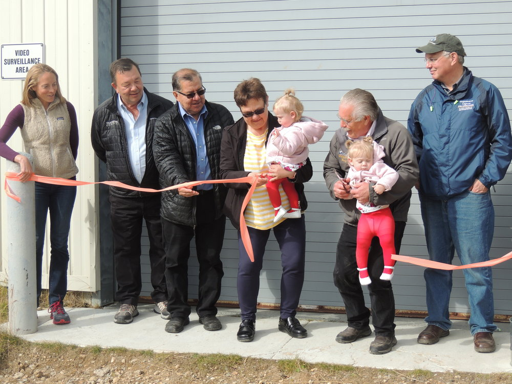 From left to right: Katie Conway, Government Relations Director for the Alaska Energy Authority (AEA); Alvin Osterback, Aleutians East Borough Mayor; Alaska Senator Lyman Hoffman; Marilyn Mack, wife of King Cove Mayor Henry Mack; King Cove Mayor Henry Mack; and Alaska Rep. Bryce Edgmon. (Henry and Marilyn Mack are holding their granddaughters, Khloe and Kambria). Photo provided by Aleutians East Borough.