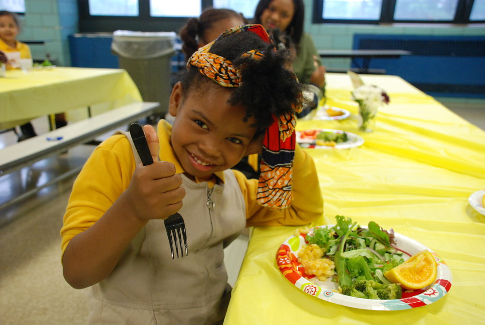 Brighter Choice: A student at Brighter Choice Community School in Bedford-Stuyvesant, Brooklyn gives a thumbs up for vegetables at a Bubble Family Meal.