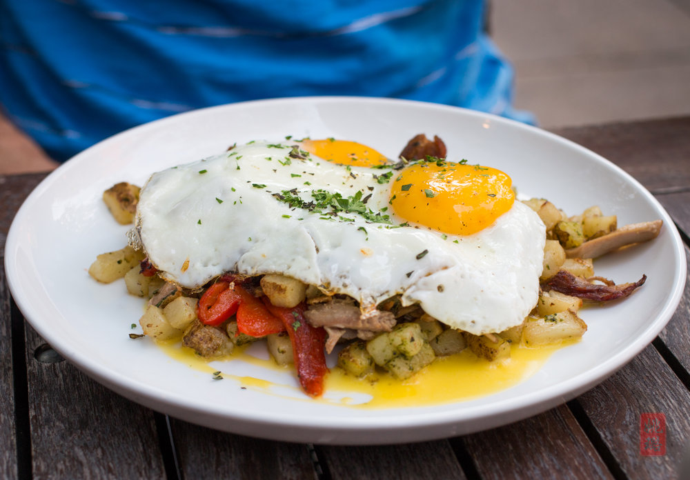 Duck hash - duck confit, shiitake mushrooms, roasted red peppers, pesto home fries, topped with sunny side eggs and hollandaise