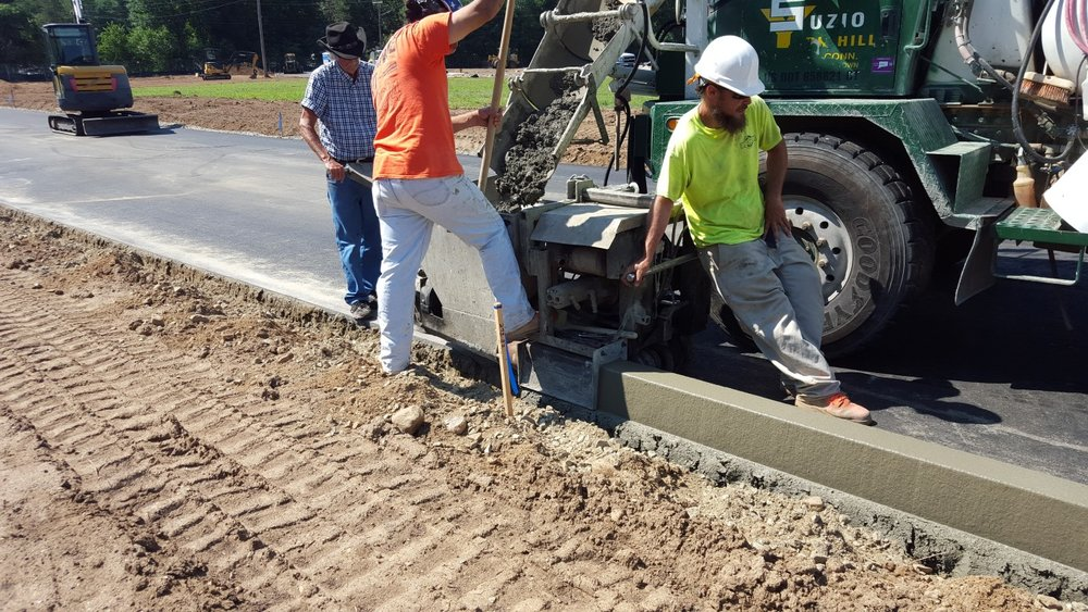 Extruded concrete curb being installed.