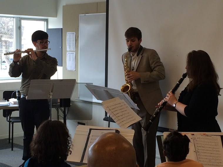 Flutist Ryan Zerna, saxophonist Richard Brasseale, and clarinetist Melissa Morales perform a woodwind trio for students at The People's Music School.