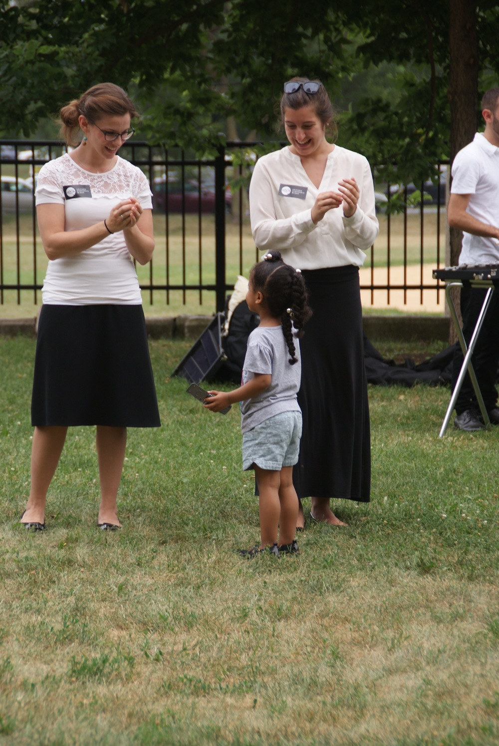 CSW volunteers help guide a young audience member through a hands-on activity as part of CSW's Shakin' It In the Parks as part of the Chicago Park District's Night Out in the Parks series.