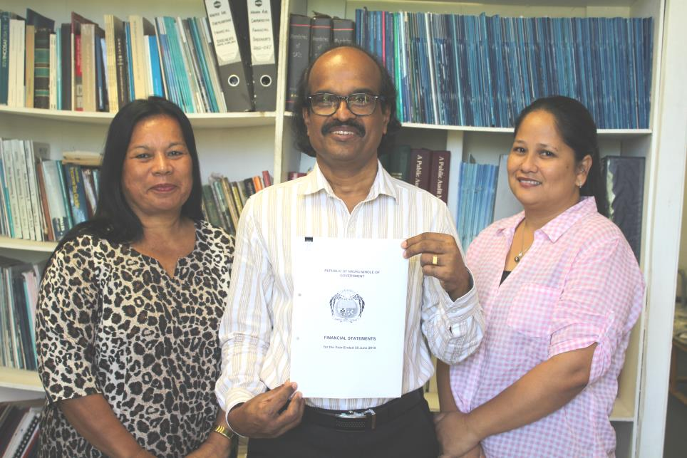 Auditor General of Department of Audit Nauru Mr Manoharan Nair holding the 2013/2014 Financial statements which includes his independent audit report, with his two audit staff Ms Gillian Itsimaera and Ms Valeni Natano