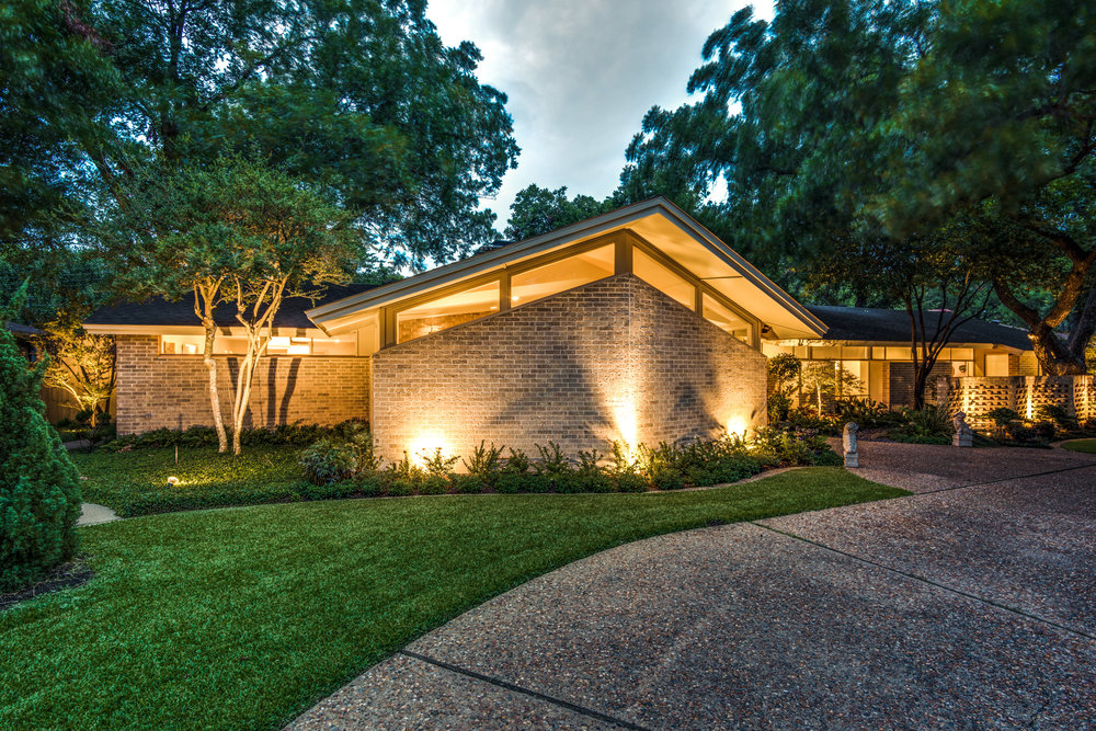 1327 Bar Harbor Drive, Dallas, Texas 75232  A grand drive up with a sleek and sexy appeal, this 1967 mid-century stunner designed by architect John Thompson has been gracefully transitioned to embrace the admired design of the era. In fact, the authenticity of the home scored it a feature on the 42nd Old Oak Cliff Conservation League Home Tour in 2015. The 3,500-square foot home integrates open spaces and brings the outdoors in. Three large mountain Junipers perfectly perched in front frame the facade of the home and balance the small Zen garden that is artfully tucked behind the perforated brick screen wall. Subtle lighting gently cascades down on the waterfall completely visible from the interior.  The best way to diminish the value of a mid-century home is to diverge from the aesthetics of the era. Thankfully, this one was updated with educated precision. The home boasts a wonderful curb appeal with its bold turquoise period front door and dramatic angles. The entry shows original brick flooring and opens to a tucked in seating salon (which could also be a dining area) carefully lit with a sputnik chandelier. The living room's vaulted ceiling, elongated brick fireplace, and transom windows preserve the mid-century drama of this home. This classic style extends to the gourmet kitchen complete with custom sleek mahogany cabinets and a marble island. Off of the main kitchen, find a clean, white catering kitchen featuring a commercial grade beverage refrigerator, deep stainless-steel sink, and ample storage—ideal for the ultimate entertainer. Visible through the glass doors of the den, the home also showcases a spectacular Zen garden, complete with multiple waterfalls and a mature pecan tree sculptured with Mondo grass for total harmony. To the right, a sun-room looks out onto the Zen yard to add a tranquil, chic spot to meditate.  Off of the entry to the private quarters is a dramatic hallway with floor-to-ceiling windows looking out into the front rock garden, which is peppered with Japanese maples and harbored by a perforated brick wall. Each of the four bedrooms have en-suite bathrooms, and, notably, the master bath has separate lavatories nicely divided by a marble frame-less shower and walk in closets on each side. The spacious master bed additionally features an off-master seating area with an original light fixture that exemplifies the striking geometric style of the mid-century era. Through the double glass doors, wake up and gaze into the grassed backyard decorated with two large urns overflowing with greenery and another beautiful water feature.  Bar Harbor is a winding street of architecturally interesting homes nestled under towering trees and located across from the Oak Cliff Country Club. This hidden gem, tucked away in beautiful Wynnewood Hills, rivals the best mid-century modern homes in Dallas. The home has been cleverly integrated with nature using ample windows and multiple areas of soothing, ambient lighting.  1327 Bar Harbor Drive will curb the carvings of any MCM aficionado.  The current owner installed one 5-ton and one 4-ton Trane HVAC unit in July of 2016. The home has a two-car garage with ample storage that opens to a rear driveway. All notable light fixtures will convey with the property, with exception to the Lalique wall sconce in the entry. Additionally, the two oversized urns with foliage will convey.
