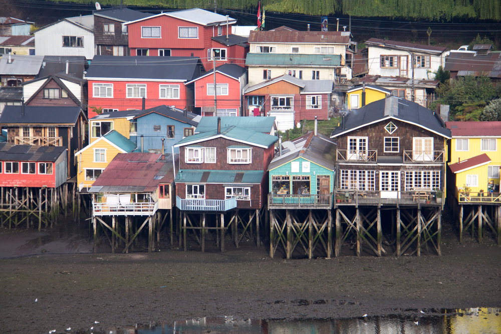 Two weeks ago we were on the grand old island of Chiloé. I was staying in one of the Palafitos (pictured), which were fishermen's houses way back in the day. Mine was the brown one on the right with the diamond shaped window at the top.