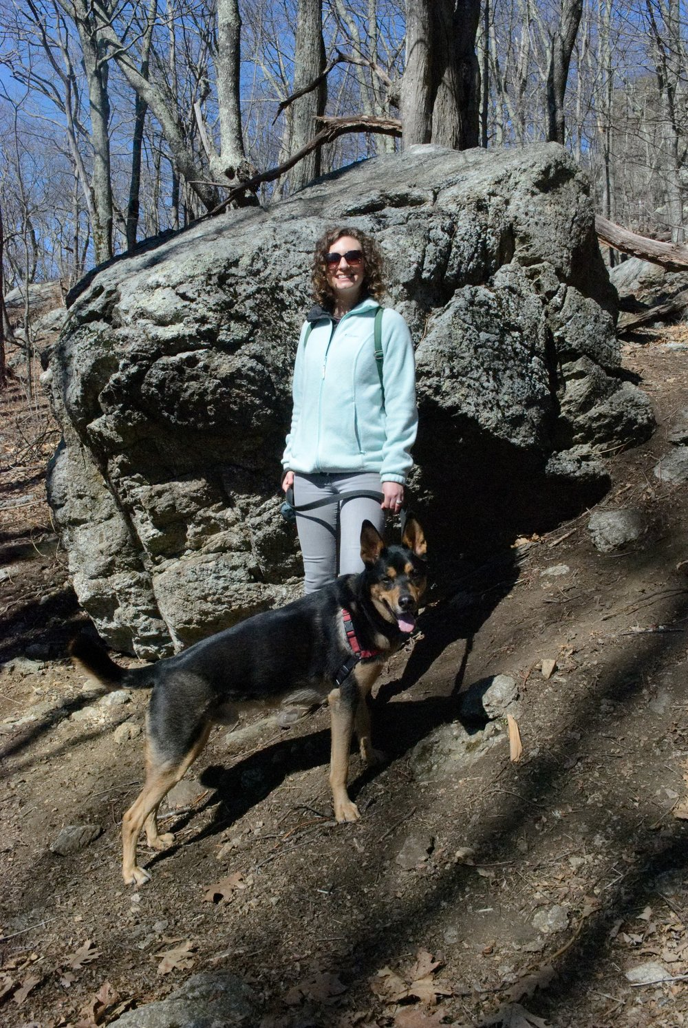 Trail wife and trail dog in front of trail boulder.