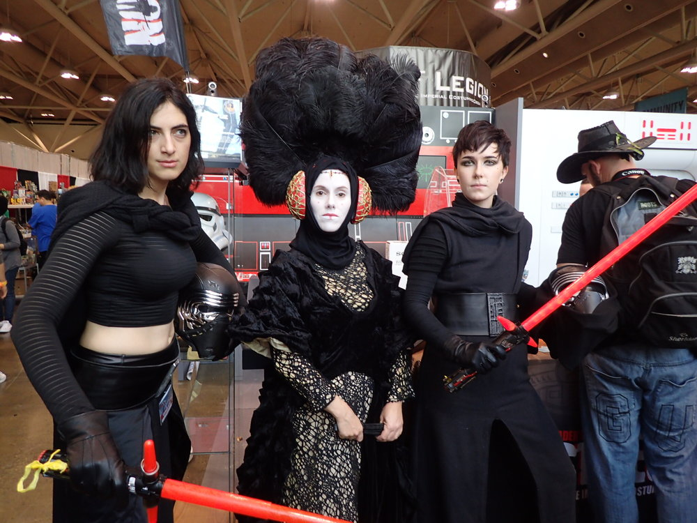 The ladies Kylo Ren pose with their grandmother. In the background you can see a guy doing what I think is a lowkey Dave Filoni cosplay.