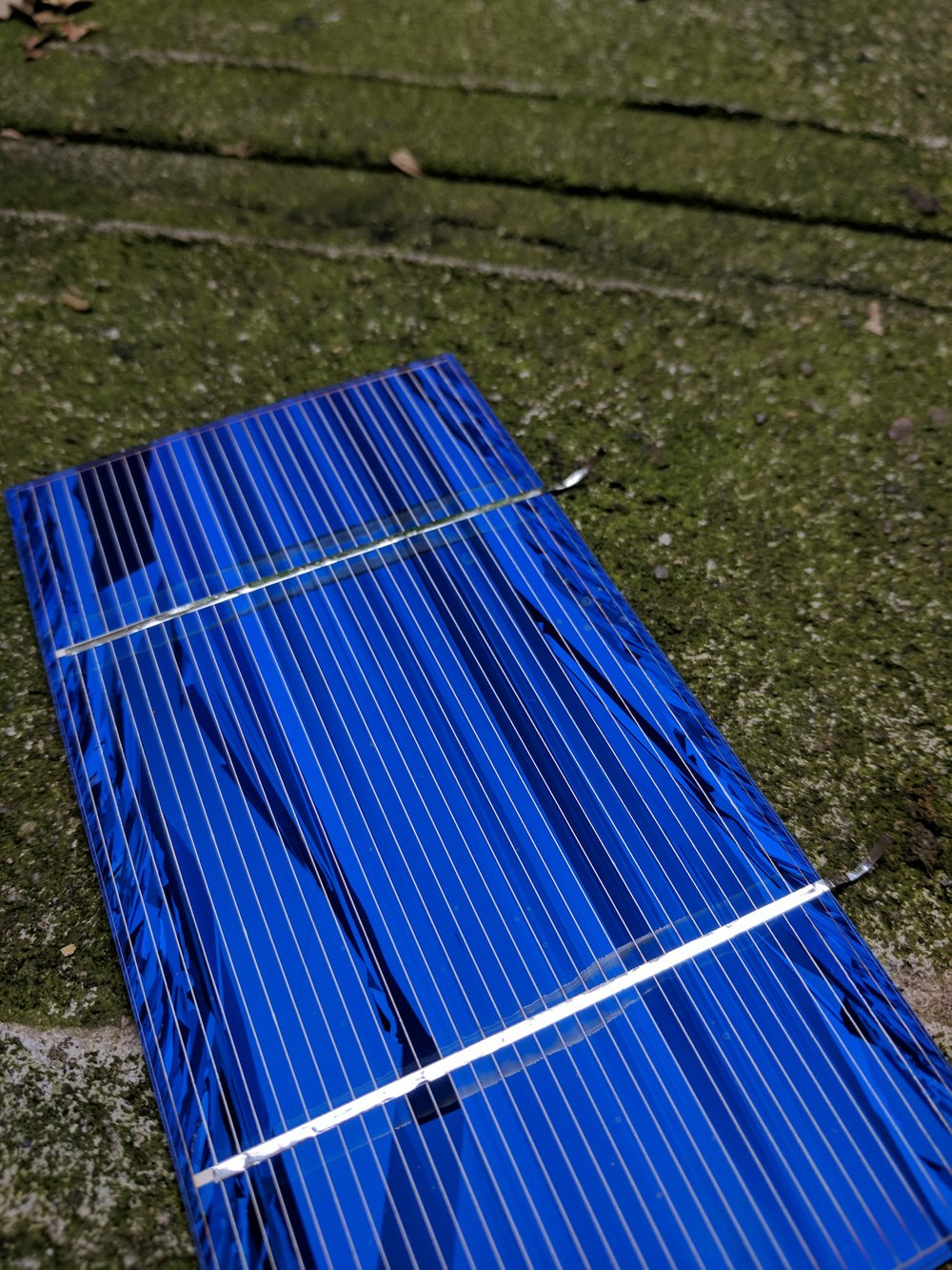 Front of solar cell. The metallic strip running across is soldered to the back of another solar cell to connect them in series and generate higher voltages.