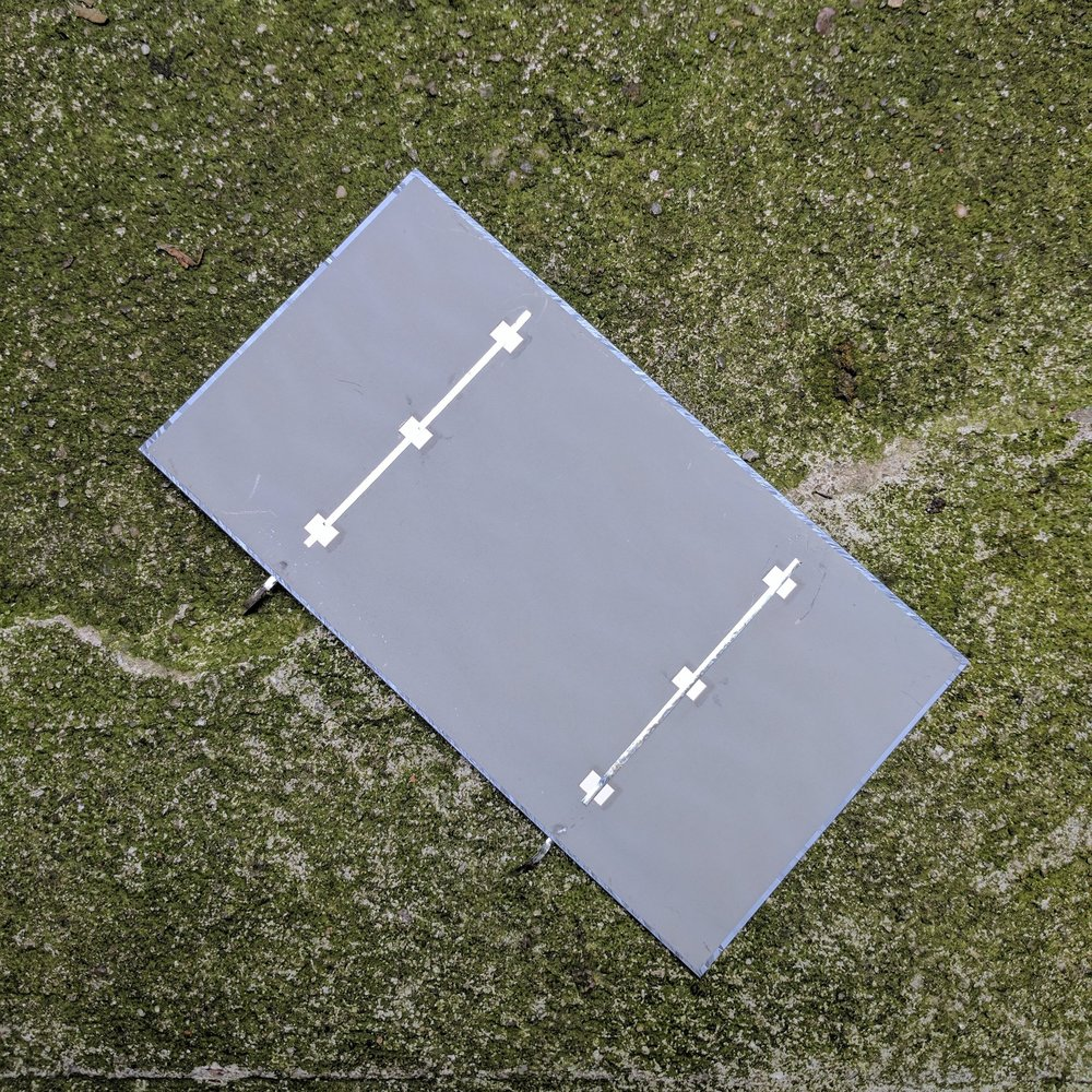 Back of solar sell. Metallic strips are soldered to pads which ultimately connect to the strips on the front of another solar cell to generate higher voltages.