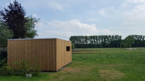 Strak tuinhuis op maat - Jabbeke   De grootte van het tuinhuis is 4 x 5 m² en heeft een verdoken deur.   Het gebruikt hout is Thermowood Larik s.