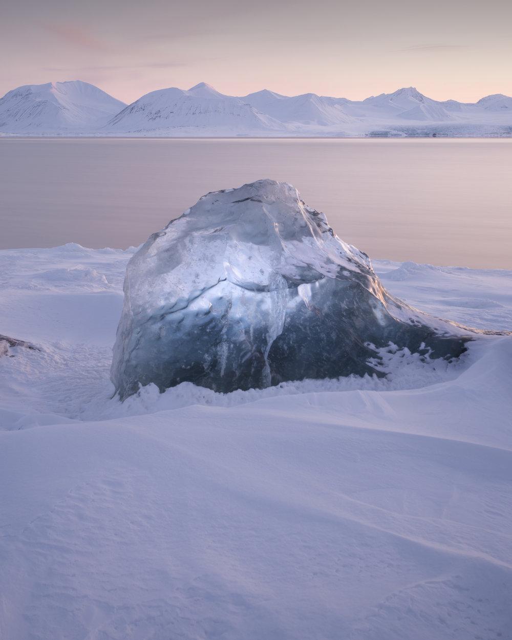 Een stuk gletsjerijs van duizenden jaren oud versiert de prachtige kustlijn in Boremorenene. Op de achtergrond kan je een gletsjer zien.