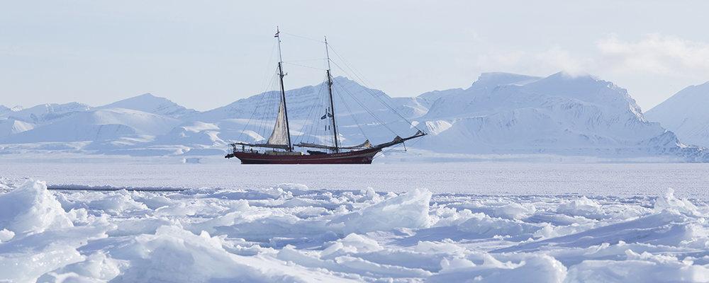 Ons schip verankerd tussen het ijs. Achterin kan je de bijboot zien die we telkens gebruikten om aan land te komen.