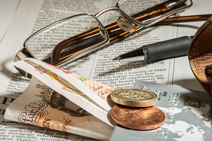 Glasses, coins, credit cards and banknotes on newspaper