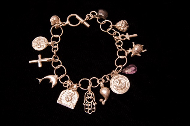 Charm bracelet: South Indian fertility bead, dog amulet, Ethiopian cross, Dolphin, Surya sun god, protective hand of Fatima, mango for abundance and fruitfulness, Swahili crescent moon and star used on the helm of dhow, amethyst healing stone, Turtle=long life, Egyptian Ankh-key of life, Ganesh Hindu elephant god- destroyer of obstacles,shell-prosperity. Silver.  Amulets vary.