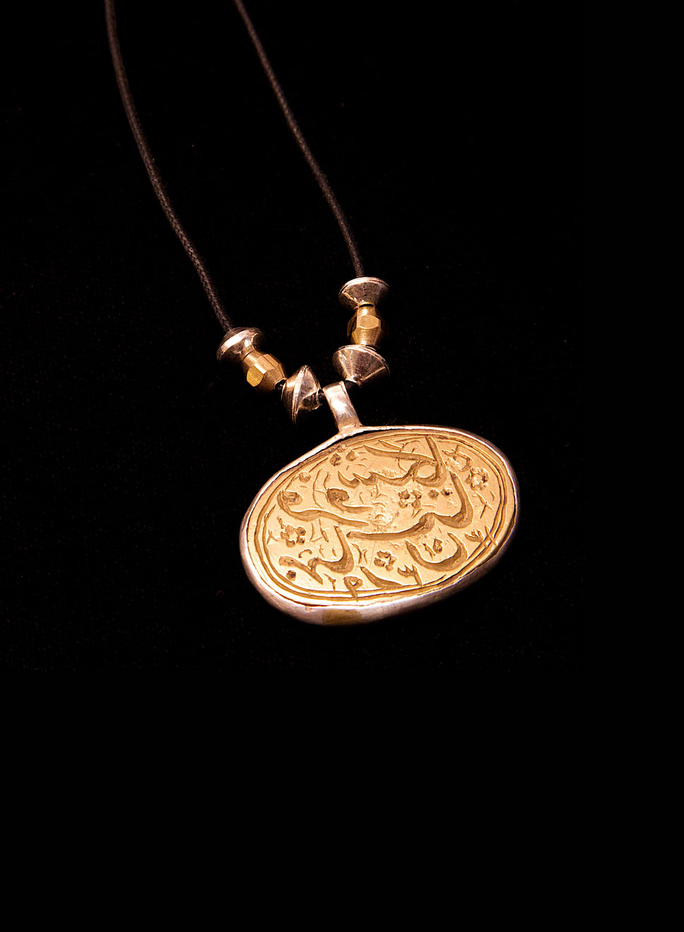 Brass antique Islamic prayer pendant set in silver on an adjustable thong. Pendant height- 4cm. Width- 5cm.