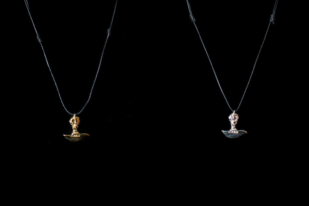 Dorje Buddhist pendant with an adjustable thong. Silver & brass. Pendant height- 2cm. Width- 2cm.