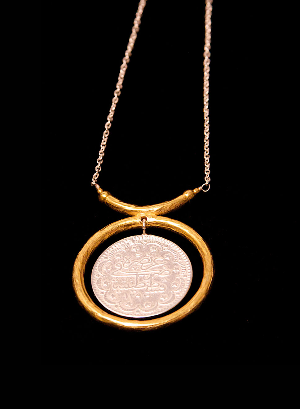 Silver Turkish coin with a silver gold plate circle and silver chain. Length of chain - 5cm. Pendant height- 4cm. Width-4cm.